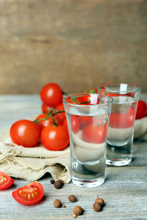 Glasses of ouzo and tomatoes on wooden table