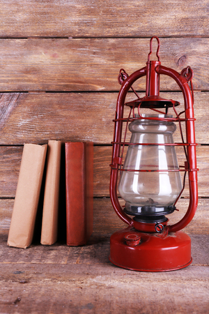 Kerosene lamp with books on rustic wooden background Stock Photo