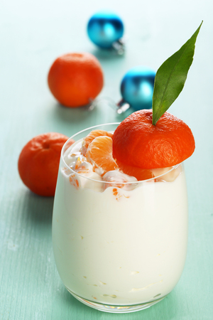 Tasty milk dessert with fresh tangerine pieces in glass, on color wooden background