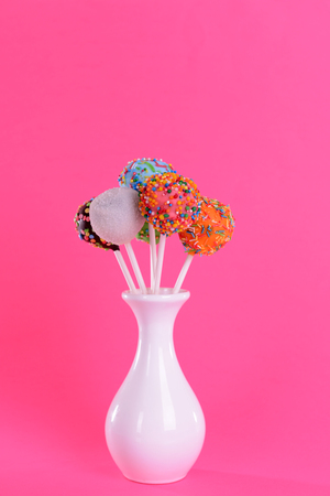 Sweet cake pops in vase on pink background Stock Photo