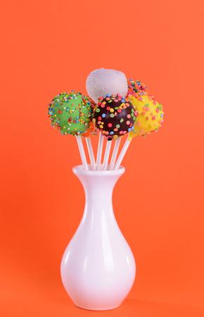 Sweet cake pops in vase on orange background Stock Photo