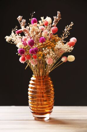 Bouquet of dried flowers in vase on table and dark background Stock Photo