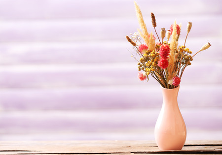 Bouquet of dried flowers in vase on color planks background