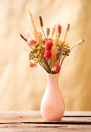 Bouquet of dried flowers in vase on color background