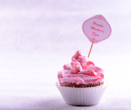 Delicious cupcake with inscription on table on beige background Stock Photo
