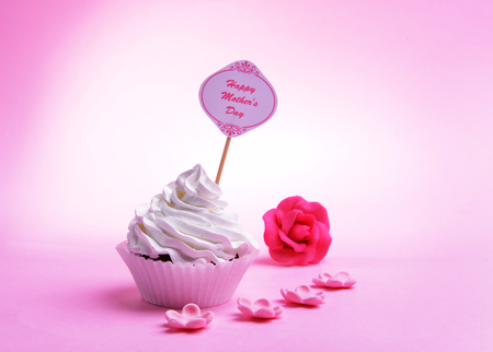 Delicious cupcake with inscription on table on pink background