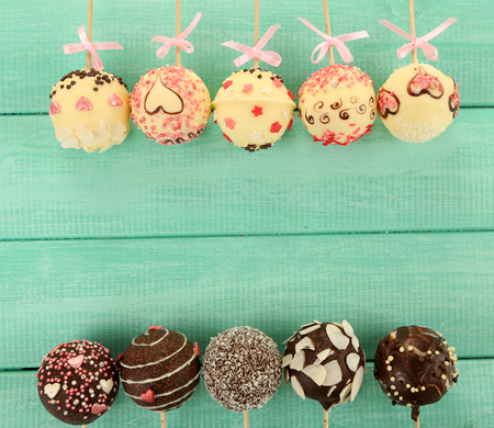 Tasty cake pops on wooden table Stock Photo
