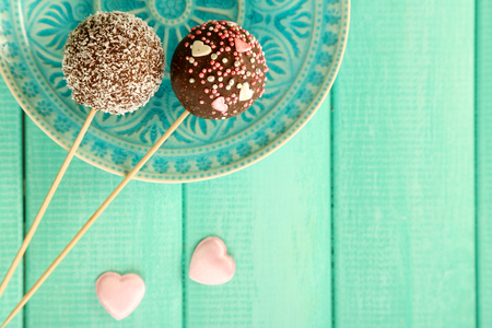 Tasty cake pops on plate, on wooden table