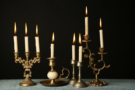 Retro candlesticks with candles on wooden table, on black background