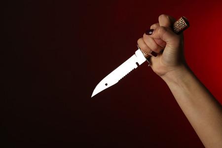 Weibliche Hand , die Messer auf rotem Hintergrund hält Standard-Bild - 99320774