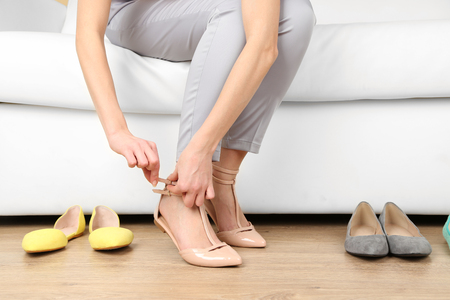 Trying on shoes by elegant lady sitting on white sofa background Stock Photo