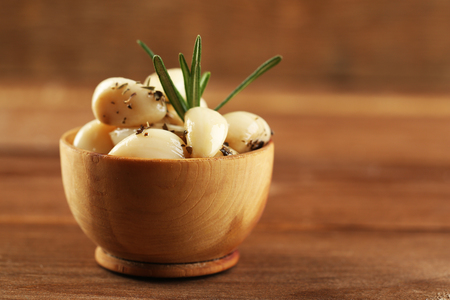 Canned garlic in bowl on wooden background Stock Photo
