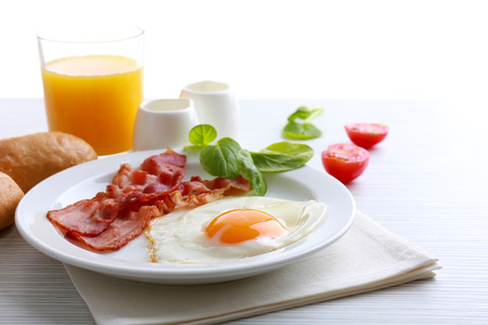 Bacon and eggs on color wooden table and white background Stock Photo