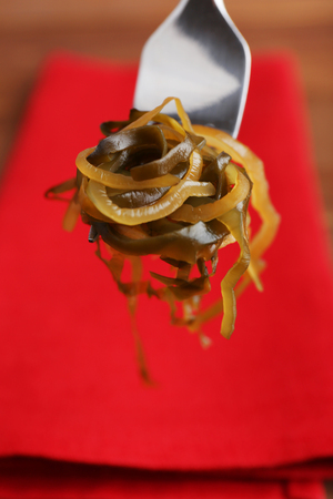 Seaweed on fork with red napkin and wooden table background Stock Photo