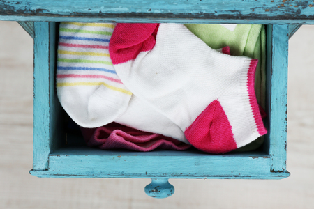 Socks in color drawer on wooden floor background Фото со стока