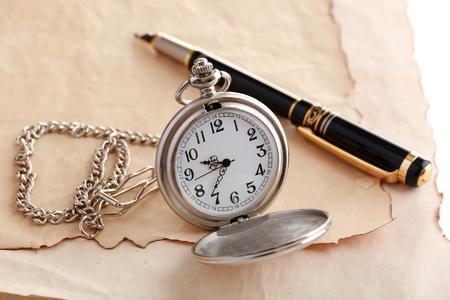 Silver pocket clock on old paper background