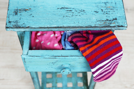 Socks in color drawer on white brick wall background 스톡 콘텐츠