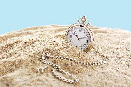 Silver pocket clock on sand on blue background Stock Photo