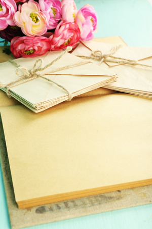 Old letters and book with flowers on wooden background