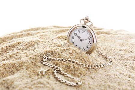 Silver pocket clock on sand isolated on white Stock Photo