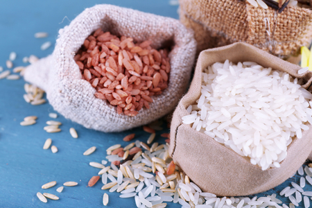 Different types of rice in sacks on wooden background Фото со стока