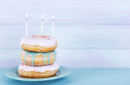 Delicious donuts with icing and birthday candles on table on wooden background