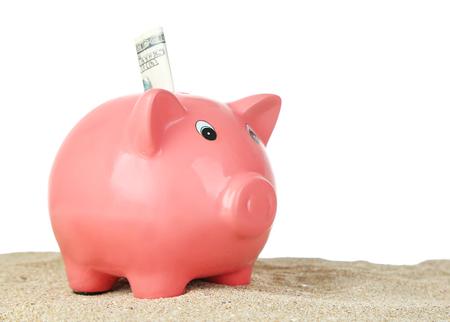 Piggy bank on sand, on white background Stock Photo