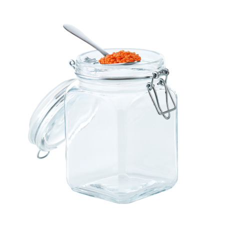 Remnants of lentils in spoon with glass jar isolated on white