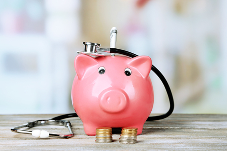 Pink piggy bank with stethoscope on light background