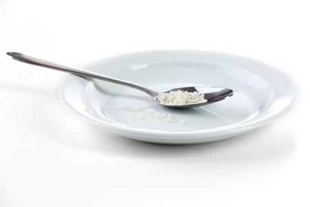 Remnants of rice in spoon on plate isolated on white Stock Photo