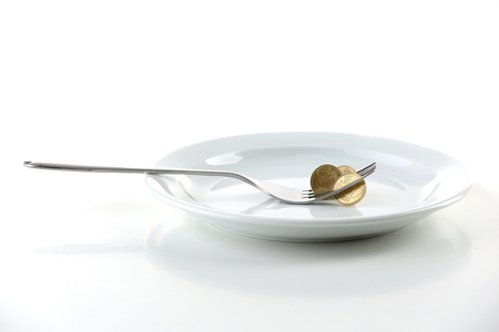 Coins on plate with fork isolated on white