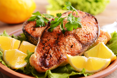 Tasty baked fish on plate on table close-up Stock Photo