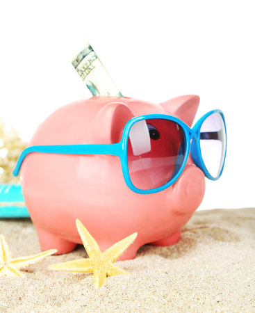 Piggy bank with sunglasses on sand, on white background Stock Photo