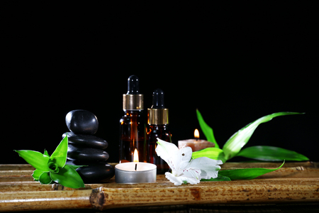 Beautiful composition with spa stones and candles on table on dark background Stock Photo