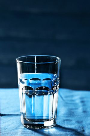 Glass of water on table on wooden background Stock Photo