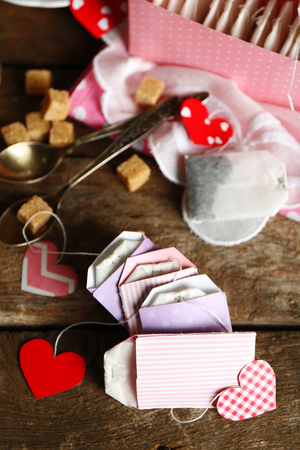 Heart shaped teabag tags and box on wooden background Stock Photo