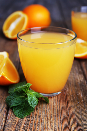 Glasses of orange juice with oranges on wooden table close up