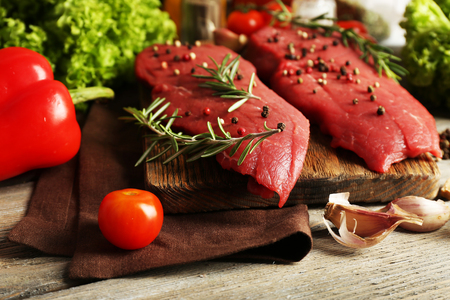 Raw beef steak with spices and greens on table close up Stock Photo