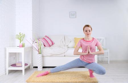 Mujer joven haciendo yoga en casa Foto de archivo