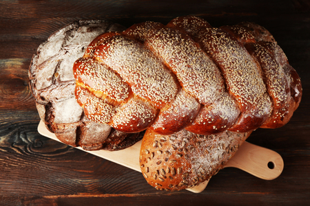 Fresh breads with bun on wooden table close up