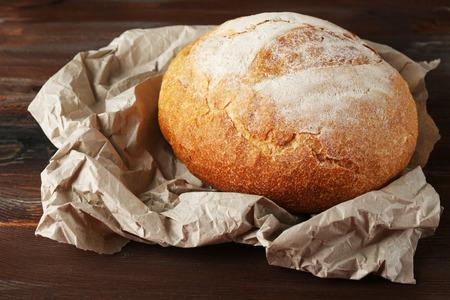 Fresh bread on paper on wooden background Zdjęcie Seryjne