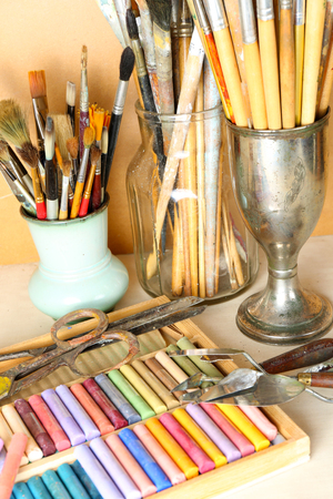 Paintbrushes with colorful chalk pastels in box on wooden background Stock Photo