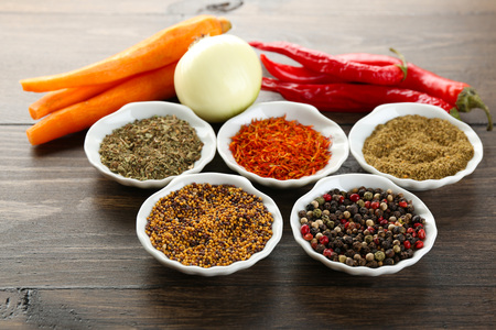 Different kinds of spices in bowls close-up, on wooden background