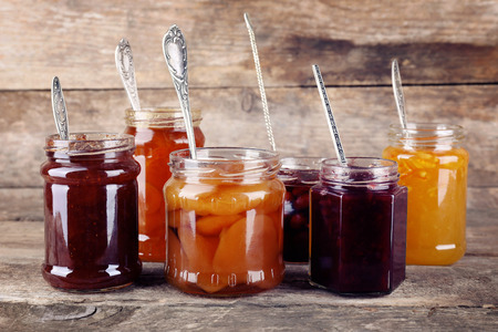 Jars of tasty jam on wooden background