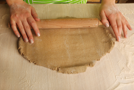 Making dough by female hands on wooden table background Stockfoto