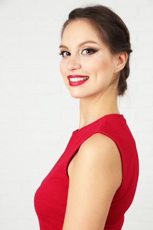Pretty woman with hairstyle in red dress on light background