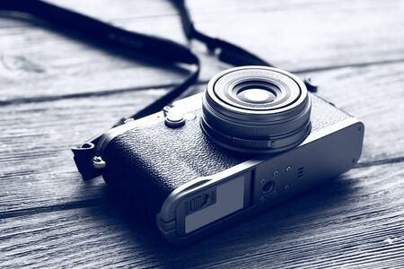 Retro camera on wooden table in shades of grey, closeup