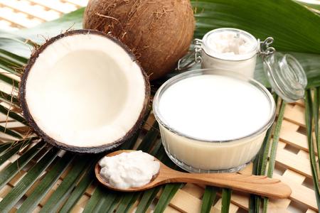Coco con hojas y aceite de coco en frasco sobre fondo de madera Foto de archivo