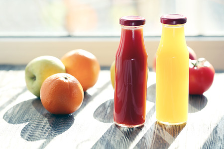 Bottles of juice with fruits and vegetables on windowsill