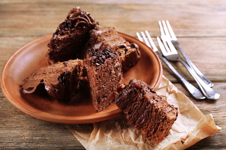 Slices of tasty chocolate cake on plate on table close up Imagens